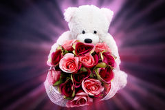 La prise de poupée d'ours un bouquet des roses rouges sur la lumière rose de rayon Photos libres de droits