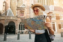 La prise et le regard de fille de voyageur tracent à Amsterdam Touriste de hippie recherchant la bonne direction sur la carte, av images libres de droits