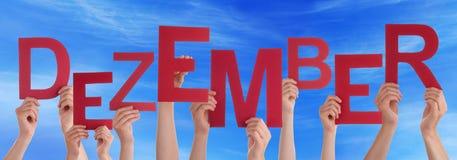 La prise Word Dezember de personnes signifie le ciel bleu de décembre Images libres de droits
