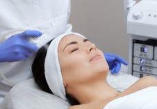 La procédure de cuire la peau à la vapeur du visage d'une jeune femme avant de nettoyer la peau photos stock