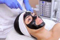 La procédure pour appliquer un masque noir au visage d'une belle femme image libre de droits