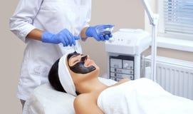 La procédure pour appliquer un masque noir au visage d'une belle femme images libres de droits