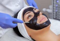 La procédure pour appliquer un masque noir au visage d'une belle femme photographie stock