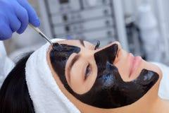 La procédure pour appliquer un masque noir au visage d'une belle femme image stock