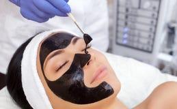 La procédure pour appliquer un masque noir au visage d'une belle femme photos libres de droits