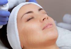 La procedura di cottura a vapore della pelle del fronte di una giovane donna prima della pulizia della pelle immagini stock libere da diritti