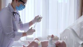 La procedura medica, l'infermiere nella maschera ed i vetri prepara il bambino per la terapia archivi video