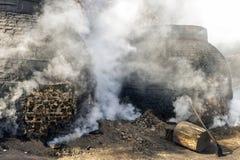 La production du charbon de bois d'une façon traditionnelle Image stock