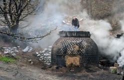 La production du charbon de bois d'une façon traditionnelle dans la forêt photo libre de droits