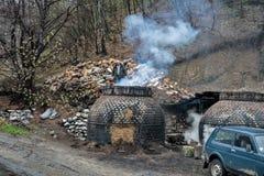 La production du charbon de bois d'une façon traditionnelle dans la forêt photos stock