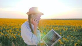 La produzione di energia, il telefono di conversazione della donna e tengono la batteria solare seguire il sole per caricare la b video d archivio