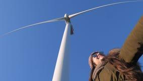 La produzione di energia, ragazza sorridente è divertentesi ed ondeggiante le armi sotto il primo piano delle turbine di energia  video d archivio