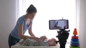 La profesión del Blogger, vlogger moderno de la madre cambia la ropa del muchacho del niño mientras que registra el vídeo de entr metrajes