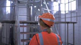 La professione tecnica per le donne, forte ingegnere femminile con la compressa in casco conduce il controllo di attrezzatura in  video d archivio