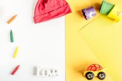 La progettazione dello scrittorio dei bambini con i giocattoli ed i vestiti ingialliscono il modello bianco di vista superiore de Fotografia Stock Libera da Diritti