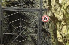 La prohibición en la fotografía del objeto Una muestra en el metal de la puerta de la entrada Las cuevas en el parque nacional Fotos de archivo