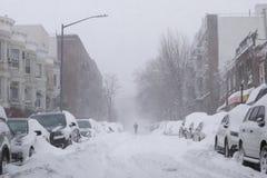 La promenade d'homme le long de la neige a couvert la rue Photographie stock libre de droits