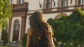 La promenade de la belle fille de sourire tournant autour dans la rue ensoleillée banque de vidéos