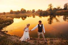 La promenade de jeunes mariés dans la perspective du lac dans le coucher du soleil rouge plan global Image stock