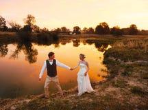 La promenade de jeunes mariés le soir dans la perspective du lac dans le coucher du soleil rouge plan global Image libre de droits