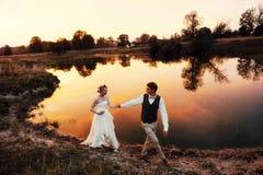 La promenade de jeunes mariés le soir dans la perspective du lac dans le coucher du soleil rouge plan global Photos stock