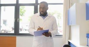 La promenade de scientifique d'afro-américain dans le laboratoire tenant des documents expliquent le plan d'expérience au collègu banque de vidéos