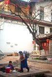 La promenade et le lavage de femme de Naxi de Chinois sur la piscine antique est le cheval blanc. image libre de droits