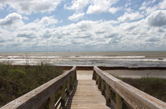 La promenade menant à la plage un jour nuageux Images stock