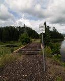 La propiedad privada ninguna muestra de violación en el tren viejo sigue la trayectoria Forest Clouds del carril fotografía de archivo