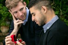La proposition d'engagement entre deux homosexuels en tant qu'un homme propose avec une bague de fiançailles dans la boîte rouge Photos stock