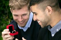 La proposition d'engagement entre deux homosexuels en tant qu'un homme propose avec une bague de fiançailles dans la boîte rouge Photo stock