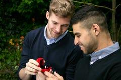 La proposition d'engagement entre deux homosexuels en tant qu'un homme propose avec une bague de fiançailles dans la boîte rouge Photos libres de droits