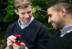La proposition d'engagement entre deux homosexuels en tant qu'un homme propose avec une bague de fiançailles dans la boîte rouge Images libres de droits