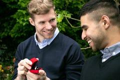 La proposition d'engagement entre deux homosexuels en tant qu'un homme propose avec une bague de fiançailles dans la boîte rouge Image libre de droits