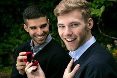 La proposta di impegno fra due omosessuali come un uomo propone con un anello di fidanzamento in scatola rossa immagine stock libera da diritti