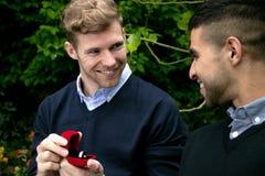 La proposta di impegno fra due omosessuali come un uomo propone con un anello di fidanzamento in scatola rossa fotografie stock libere da diritti
