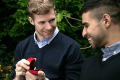 La proposta di impegno fra due omosessuali come un uomo propone con un anello di fidanzamento in scatola rossa immagini stock