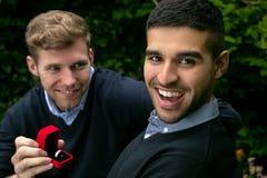 La proposta di impegno fra due omosessuali come un uomo propone con un anello di fidanzamento in scatola rossa fotografie stock