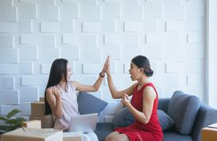 La propriétaire de femme de petite entreprise soulèvent vers le haut de eux des mains et travailler à la maison le bureau, affair photo stock