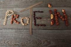 La proteína de la palabra se compone de la comida: tallarines del soba, cacahuetes, garbanzos, habas, avellanas, nueces de Brasil Fotografía de archivo libre de regalías