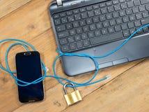 La protección del ordenador y el teléfono móvil con aseguran la cerradura imágenes de archivo libres de regalías