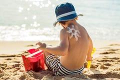 La protección solar del dibujo del sol, loción del bronceado en la parte posterior del bebé El niño caucásico se está sentando co Fotografía de archivo libre de regalías