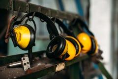La protection auditive et le contruction de casque antichoc placé sur le plancher en bois représente le concept de garder la qual image libre de droits