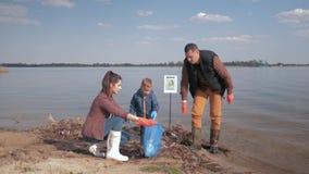 La protection de la nature écologique, garçon d'enfant aide les activistes volontaires de parents à nettoyer le remblai sale de r clips vidéos