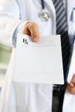 La protection masculine de presse-papiers de prise de main de docteur de médecine et donnent le prescripti Images stock