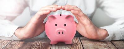 La protezione consegna il porcellino salvadanaio rosa - concetto di sicurezza finanziaria immagini stock