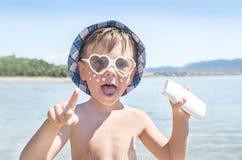 La protezione solare è sul fronte del ragazzo dei pantaloni a vita bassa prima dell'abbronzatura durante la vacanza estiva sulla  Immagini Stock Libere da Diritti