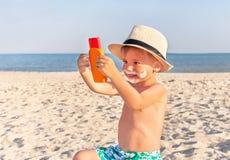 La protezione solare del disegno dei baffi sul fronte del bambino (ragazzo) fotografia stock