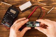 La prova e ripara il chip per servizio per mezzo di un tester e un insieme dell'ingegnere elettronico fotografie stock