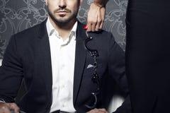 La prova sexy della donna seduce l'uomo d'affari ricco sul sofà fotografie stock libere da diritti